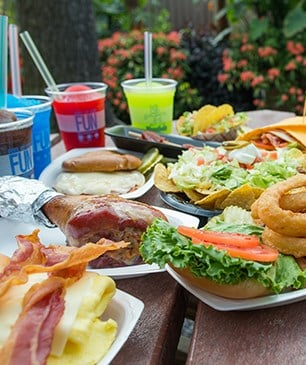 A table of hamburgers and drinks.